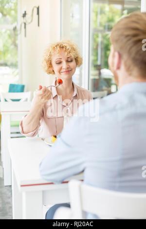 Sonriente mujer rubia comer sentado a la mesa con un hombre en restaurante.