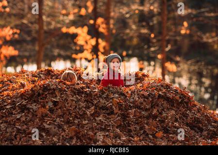 Dos niños sentados en el medio de un montón de hojas, Estados Unidos