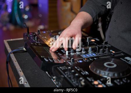 Las manos del hombre pulse los botones en el control remoto, DJ hace música . DJ's manos a la mezcla de la música en una fiesta - jugar algunas bellas canciones para los huéspedes