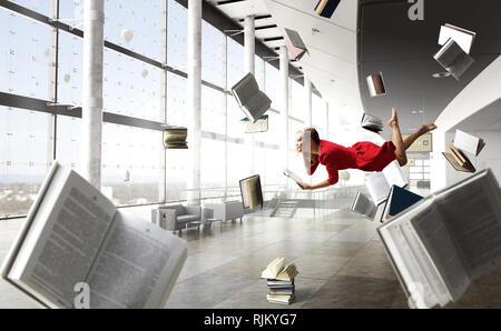 Relajado mujer levanta en la habitación llena de libros de vuelo. Mixed Media Foto de stock