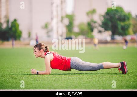 Tema deporte y salud. Joven mujer caucásica haciendo el warm-up, calentando los músculos, el entrenamiento de los músculos abdominales. Perder barriga. Ejercicio sobre tablones abdominal