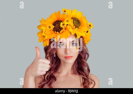 Feliz joven con diadema floral mostrando Thumbs up como signo de mano. Niña con corona de girasoles en la cabeza aislado sobre fondo gris con CDP Foto de stock