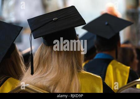 Los estudiantes que vestían trajes y gorros sentarnos adentro, esperando recibir diplomas, día de graduación en la universidad, colegio inicio
