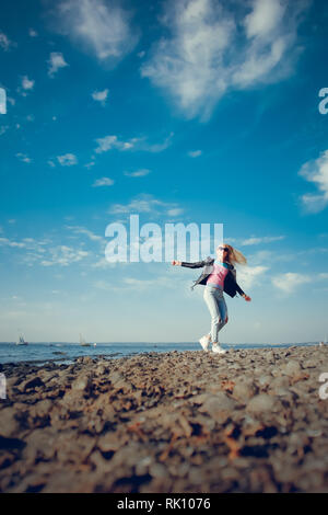 Chica rubia con gafas negras y jeans posando en la playa Foto de stock