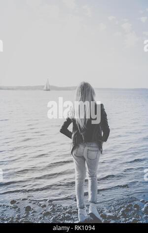 Fotografía en blanco y negro de una niña esperando en la playa Foto de stock