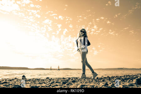 Chica rubia con el pelo largo en una sesión de fotos en el mar Foto de stock
