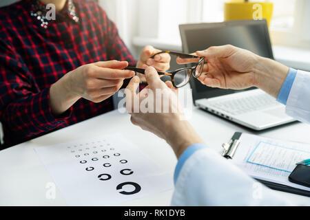 Optometrista visita - mujer obtenga sus nuevas gafas en la oficina óptico