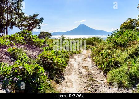Carretera de terracería que conduce al Lago Atitlán con el volcán San Pedro en el fondo, el altiplano de Guatemala, Centroamérica Foto de stock