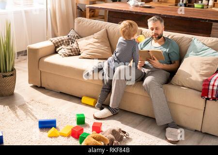 Padre libro de lectura mientras que su hijo pidiéndole que juegue con él
