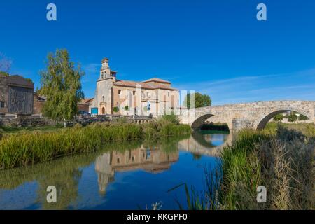 Iglesia de Santa Cristina y el puente romano de piedra, se reflejan en el agua del río Ucero, Landmark y el monumento público en el Burgo de Osma, Soria, España,