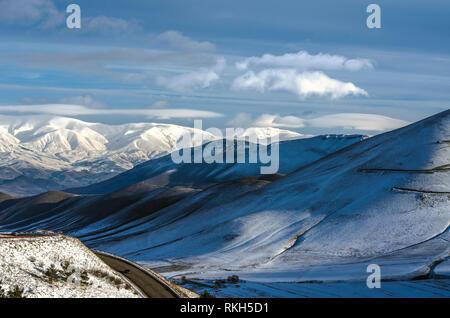Vista de los giros en el camino hacia la ciudad de Spitak y los primeros rayos del sol de invierno, la dispersión de la niebla en las montañas de Aragats