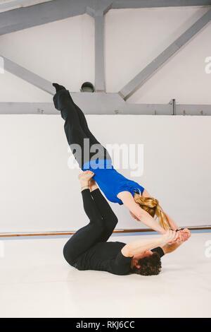 El tema es Deporte y superficie. Una joven pareja macho y hembra caucásica practicando yoga acrobático en un gimnasio blanco sobre esteras. Un hombre yace sobre su espalda y hol Foto de stock