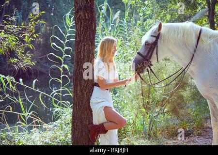 Chica rubia feed pasto para su caballo blanco en un mágico bosque de luz cerca del río.