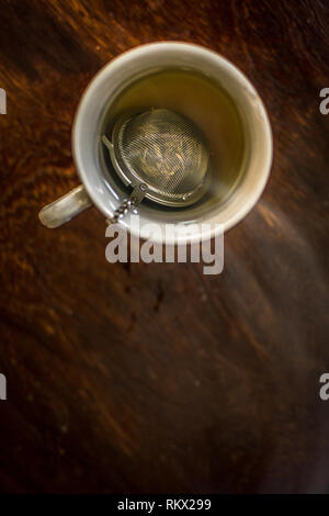 Taza de Té con infusor ahumado en caliente el agua con té verde, menta, hierbas y miel sobre un fondo de madera oscura. Foto de stock