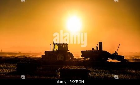 Plano amplio de la silueta de tractor agrícola al amanecer.