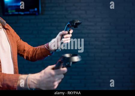 Hombre juego de realidad virtual utilizando gamepads en el cuarto oscuro del club jugando, vista cercana se centró en manos