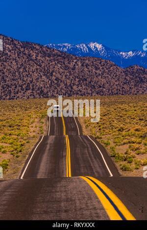 Un camper van pasando a lo largo de la autopista 120 en California después de venir de Nevada con detrás de las montañas de Sierra Nevada, Estados Unidos.