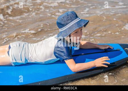 Happy Baby Boy - joven surfista paseo en tablas de surf con la diversión en las olas del mar. Active la vida familiar, los niños piscina deporte acuático lecciones y actividades de natación