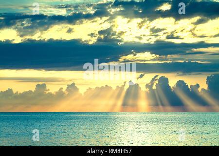 Hermoso paisaje del mar con un atardecer. Atardecer cielo con nubes y rayos de sol sobre el océano. Rayos de sol brillan romper a través de las nubes