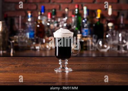 Calentar el Whiskey Irlandés Cóctel de café en una barra.