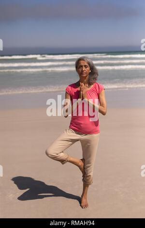 Mujer mayor con los ojos cerrados y las manos entrelazadas haciendo yoga en la playa
