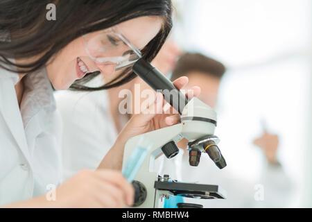 Close up.El científico se ve en el microscopio en el laboratorio.