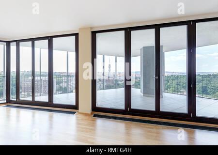 Moderno apartamento loft blanco y vacío interior con suelo de parquet y ventanas panorámicas con vistas a la urbe Foto de stock
