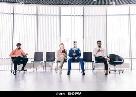 Gente ejecutivos en trajes fashipn pasar tiempo con sus gadgets.waitness.