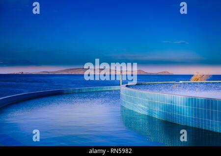 Tonos de azul, donde el azul artificial de la piscina se encuentra con el azul profundo del mar y el cielo.