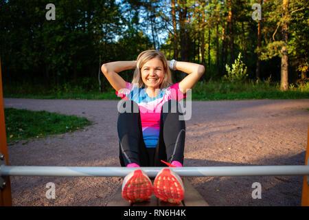 Atleta rubia con las manos detrás de la cabeza practicando en banco de madera en el parque en verano.