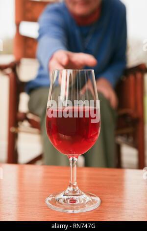 Una mujer sentada superiores llegando a recoger un vaso de vino tinto en una tabla en la parte delantera. UK