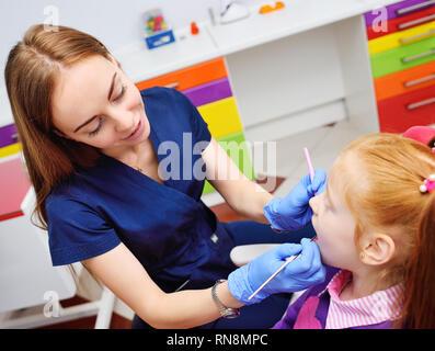Children's dentista le examinará los dientes y la boca del niño - una linda chica pelirroja sentada en un sillón dental