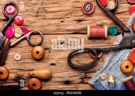 Carretes de hilo y herramientas básicas de costura en tablero de madera