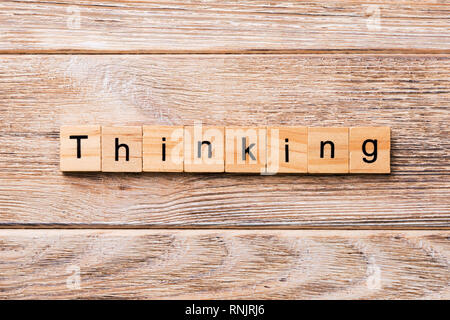 Pensando palabra escrita sobre un bloque de madera. Pensando en texto en tabla de madera para su diseño, concepto.