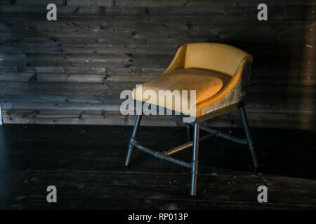 Taburete de metal con tapicería suave en estilo loft contra una pared de madera. Espacio libre para el texto.