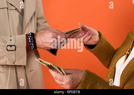Vista recortada de alto par la celebración de billetes de dólar en manos aisladas sobre naranja