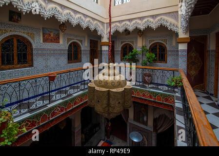 Patio interior con azulejos en las paredes y el piso de mosaico. Vistoso y tradicionales coloridos arabescos tallados en la pared sobre una arcada en riad marroquí