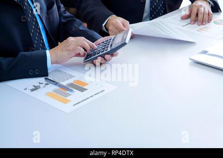 Dos hombres de negocios están profundamente revisar informes financieros para un retorno de la inversión o el análisis de riesgo de inversión en un escritorio en blanco. Copia inferior derecha spac