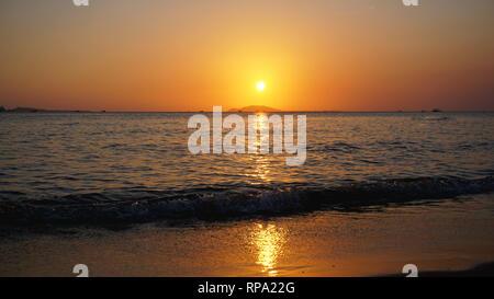 Atardecer con brillante sol amarillo bajo la superficie del mar - vacaciones de verano y la naturaleza concepto de viaje de aventura. Foto de stock
