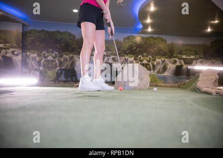 Una mujer joven en zapatillas blancas jugando al mini golf en interiores
