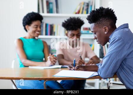 Profesora de aprendizaje con los estudiantes afroamericanos en el aula de la escuela