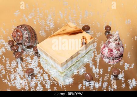Crema de vainilla y café pastel de ratón sobre un espejo de hielo sobre un fondo claro Foto de stock