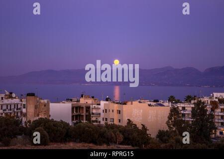 Púrpura atardecer sobre la bahía. Twilight Hersonissos. Full moon rising paisaje. Paisaje urbano por la noche. Los edificios, el Mar Mediterráneo y las montañas. La isla de Creta. Foto de stock