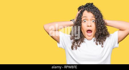Hermosa mujer joven con el pelo rizado vistiendo camiseta blanca loco y asustado con las manos en la cabeza, asustados y sorprendidos de shock con la boca abierta Foto de stock