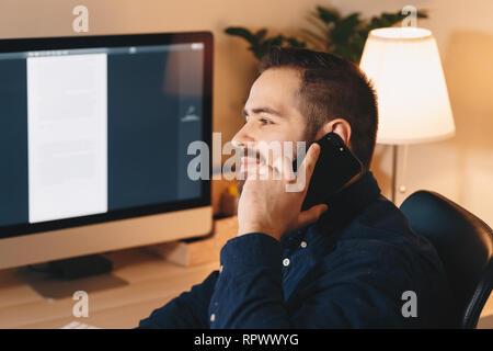 El empresario moderno y atractivo en su hogar, oficina, usando su teléfono móvil mientras está sentado en una silla frente a su lugar de trabajo personal