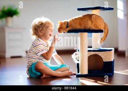Niño jugando con el gato en la casa. Los niños y las mascotas. Niñito alimentar y acariciar a color jengibre lindo gato. Gatos y scratcher árbol en el salón interior.