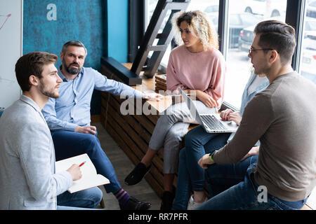 Hermosa gente de negocios es el uso de gadgets, hablando y sonriendo durante la conferencia en la oficina.