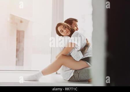 Hermosa joven pareja romántica abrazarse y sentada sobre el alféizar de la ventana en el hogar con espacio de copia
