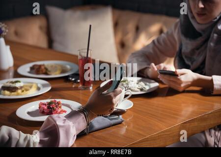 Dos mujeres musulmanas sentarse con los gadgets en una mesa en un restaurante Foto de stock