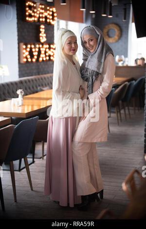 Dos jóvenes musulmanas de pie en la cafetería Foto de stock